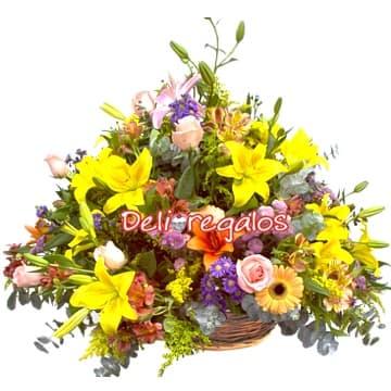 Diloconrosas.com - Fantasia con rosas - Codigo:AGF18 - Detalles: Radiante composicion floral en base de mimbre compuesta por gerberas en tonos amarillos, iris, margaritas, boton de oso, azucenas  y 6 rosas importadas, flores y follaje de estacion.  - - Para mayores informes llamenos al Telf: 225-5120 o 476-0753.