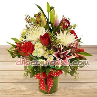 Diloconrosas.com - Arreglo en base de ceramica a base de 5 rosas importadas, 4 liliums flores y follaje de estacion. El presente incluye una tarjeta de dedicatoria. - Atendemos 24 horas. Llamar al 225-5120 o via Whatsapp: 980-660044